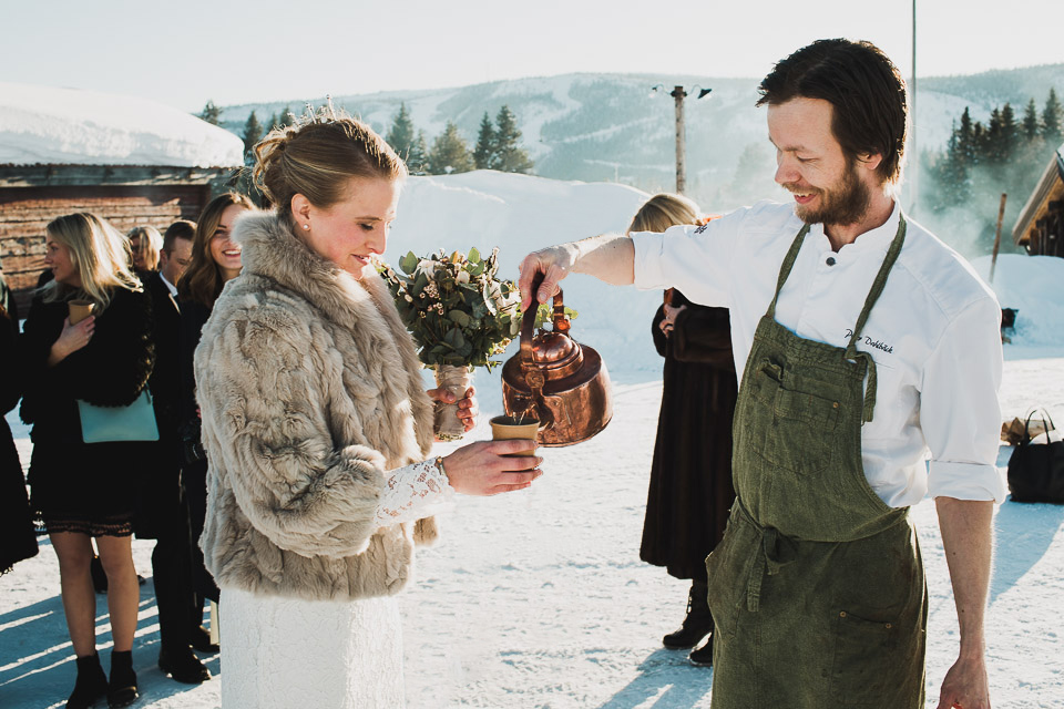 Brud blir serverad dryck i vinterlandskap