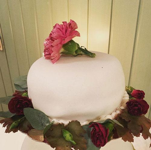 Bröllopstårta med rosa och röda blommor