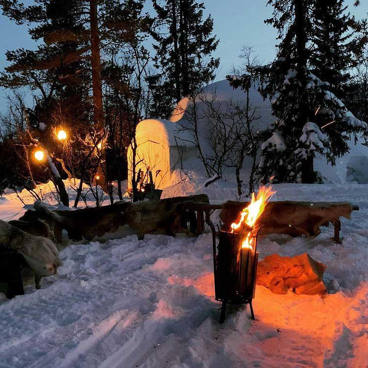Brasa ute i snön med en igloo i bakgrunden