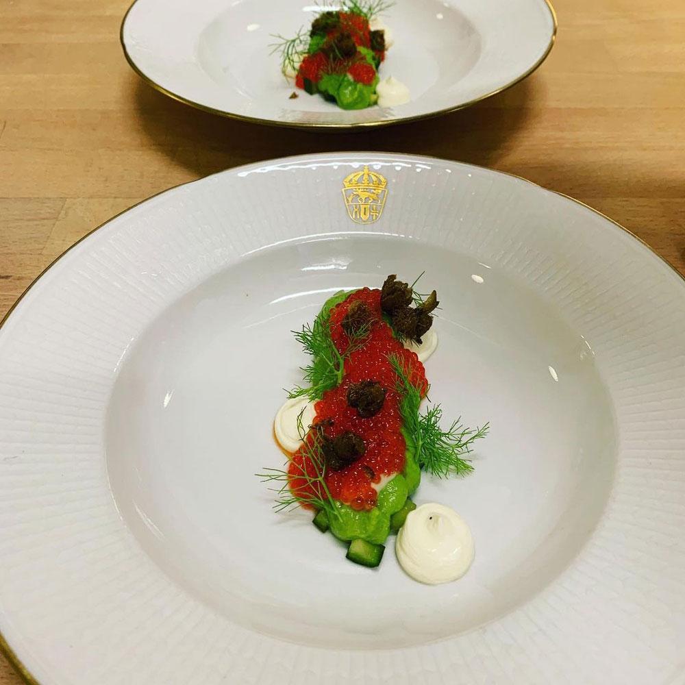 Fint upplagd mat, toppad med rom, på kungligt porslin
